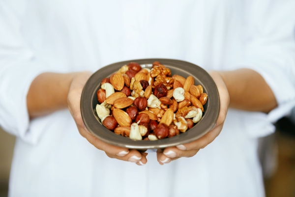 Healthy Food. Hands Holding Bowl With Nuts. Close Up Of Female Holding Plate With Different Types Of Nuts. Healthy Fats For Nutrition And Diet. High Quality