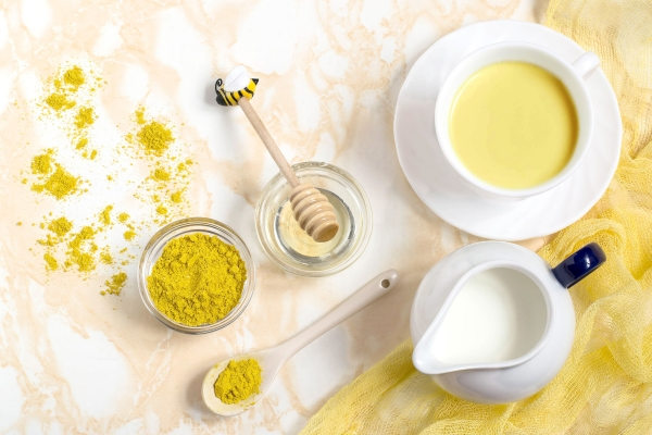 Healthy drink: milk with turmeric and honey, known as the golden milk. Detox, burns fat, boosts immunity, disease prevention. Flat lay, top view