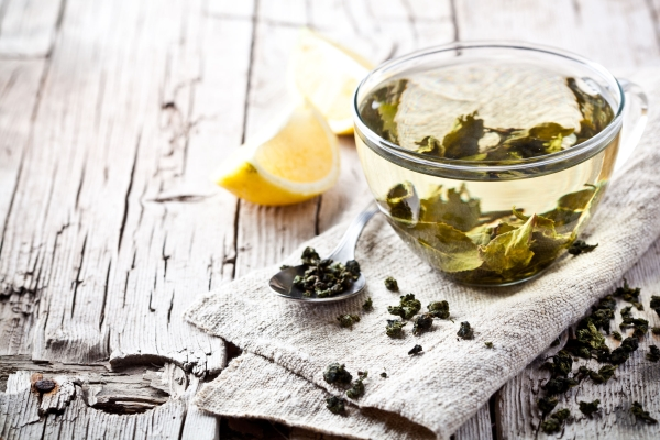 28711690 - cup of green tea and lemon on rustic wooden table
