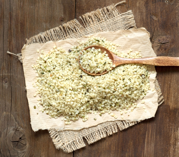 Hemp seeds with a spoon on a wooden table