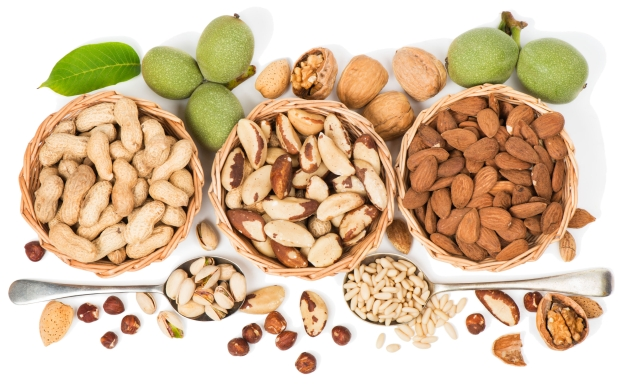 Assorted nuts in a wicker bowl isolated on a white. View from above.