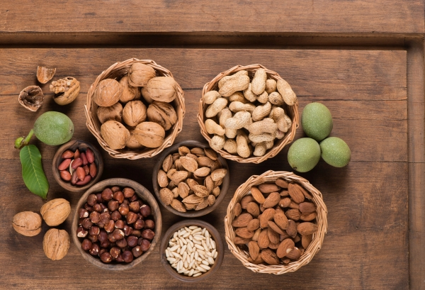 Assorted nuts (walnut,  almond, peanut, pine nuts, hazelnut) in a wooden bowls and baskets