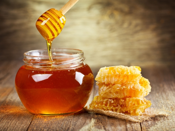 26015645 - jar of honey with honeycomb on wooden table