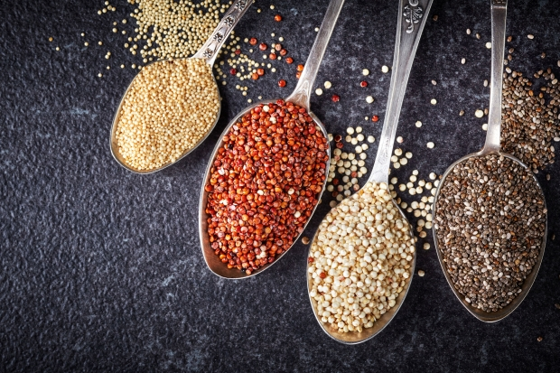 37509268 - collection of healthy seeds in silver spoons on dark background
