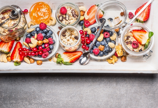 Oatmeal with berries and nuts in glass jars, top view. Healthy breakfast , sports nutrition or diet food concept