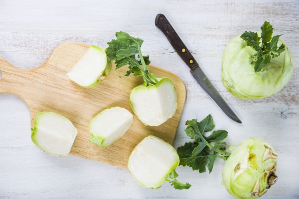 Chopped kohlrabi and knife on chopping board on a wooden table, top view.  Delicious cabbage close-up, healthy eating.