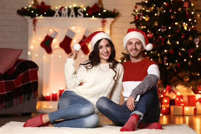 Young couple in santa hats sitting at home near christmas tree