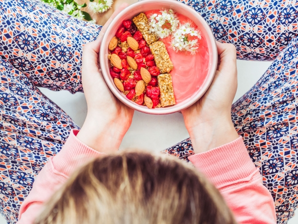 Berry smoothie, muesli with nuts, dry berries, pieces of banana, beautiful, blooming flowers in a pink plate and and a young woman. Concept of healthy and tasty food
