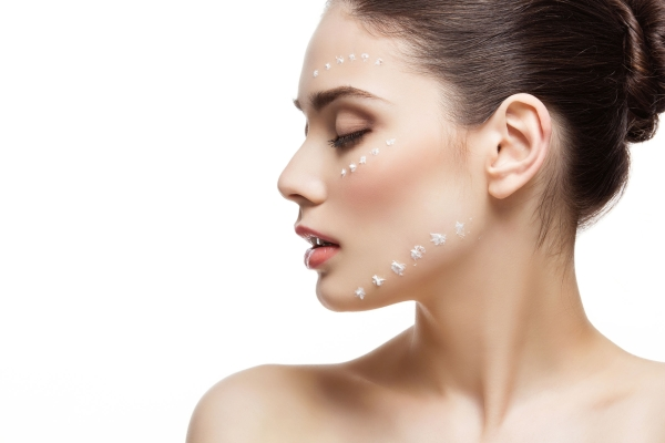 Beautiful young woman with moisturizing cream dots on face. Isolated over white background. Copy space.