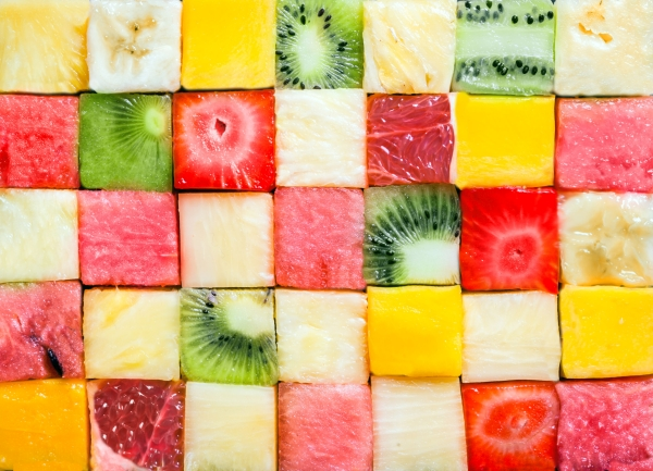 Seamless background pattern and texture of colourful fresh diced tropical fruit cubes arranged in a geometric pattern with melon, watermelon, banana, pineapple, strawberry, kiwifruit and grapefruit