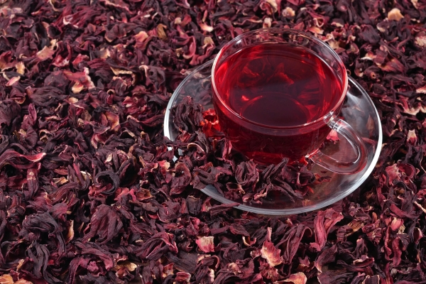 Cup of hibiscus tea in a heap of dried petals of hibiscus