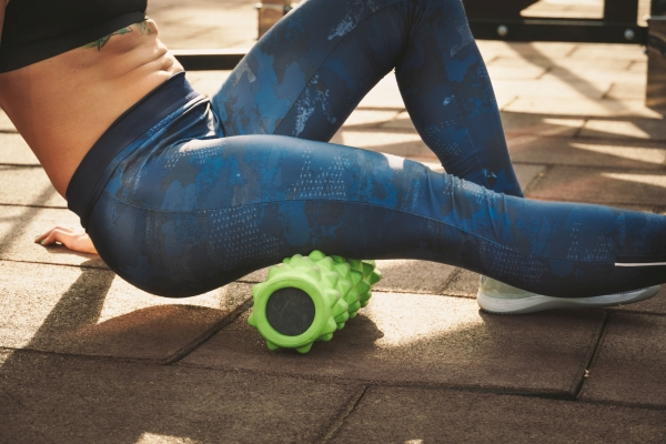 theme sport and rehabilitation sports medicine. Beautiful strong slender Caucasian woman athlete uses foam roller green field street workout to workout to remove pain, stretch and massage muscles.