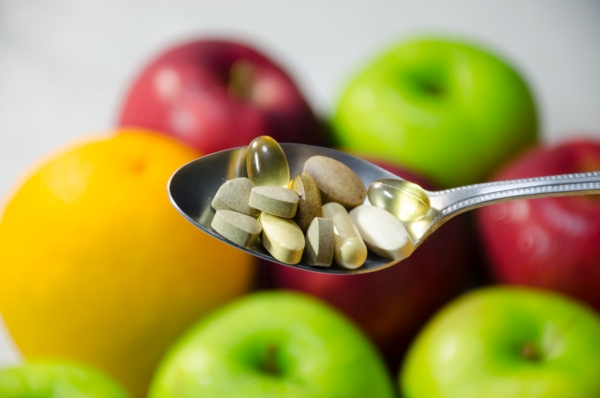 Assorted vitamins and nutritional supplements in serving spoon. on blur colorful fruits background