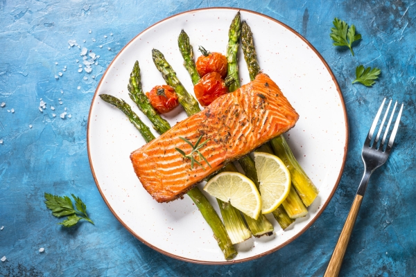 Grilled salmon fish fillet with asparagus. Top view on blue stone table.