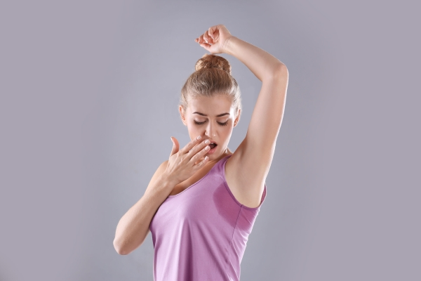 Young woman with sweat stain on her clothes against grey background. Using deodorant