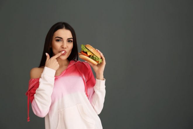 Young woman eating tasty burger on grey background. Space for text