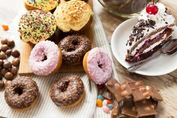 junk food, culinary, baking and eating concept - close up of glazed donuts, cakes and chocolate sweets on table