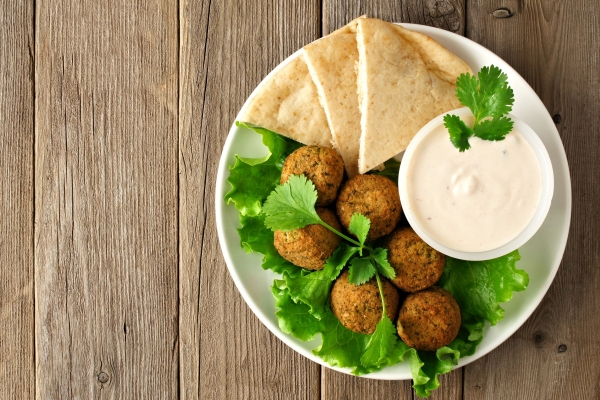36064591 - plate of falafel with pita bread and tzatziki sauce on wooden table. view from above