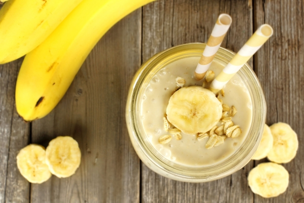 37377218 - banana oatmeal breakfast smoothie in mason jar on wood table, downward view