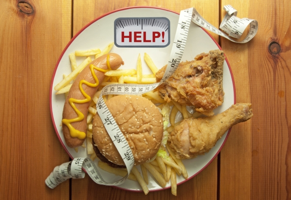 Plate packed with junk food with weighing scales help sign