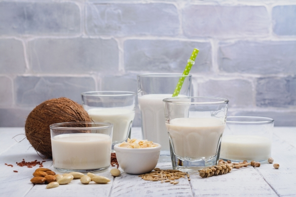 Assortment of non dairy vegan milk and ingredients on white wooden background. Healthy drinks concept. Copy space