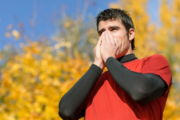 16467692 - young athlete coughing and blowing with a tissue. caucasian hispanic male model.