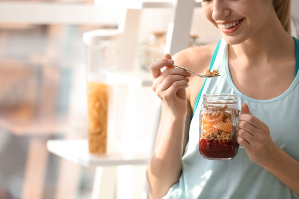 Young woman in fitness clothes having healthy breakfast at home, closeup. Space for text