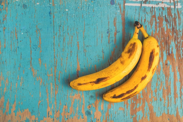 Two old ripe bananas on rustic wooden table, top view