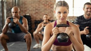 Group of fit people holding kettle bell during squatting exercise at cross training gym. Fitness girl and men lifting kettlebell during strength training exercising. Group of young people doing squat with kettle bell.