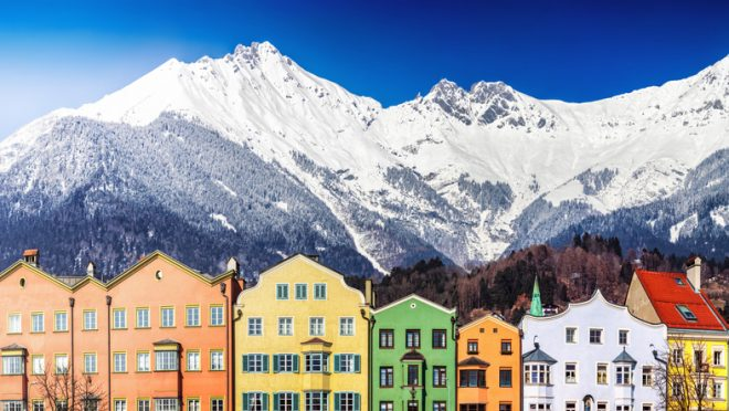 Panoramic cityscape of Innsbruck downtown street houses (Mariahilfstraße) with Alpine mountains peaks on sunny winter day