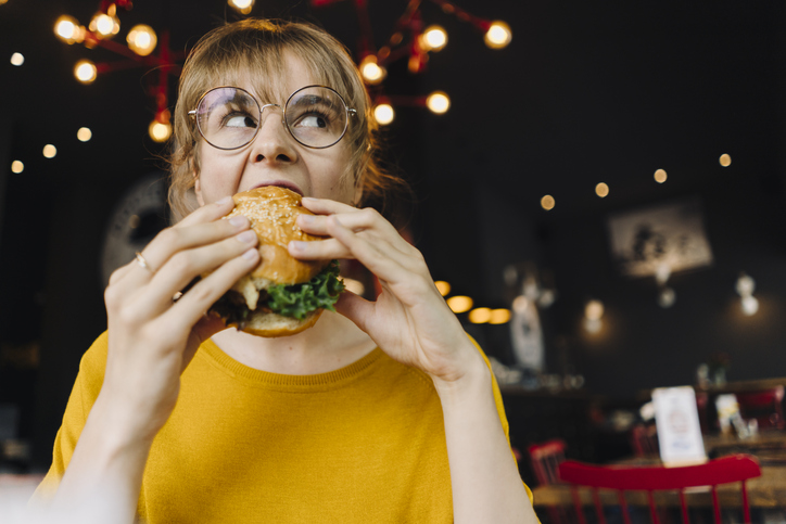 Young woman eating burger in a restaurant