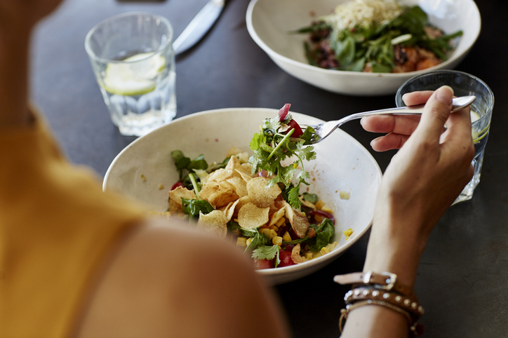 Cropped image of woman having food at restaurant table